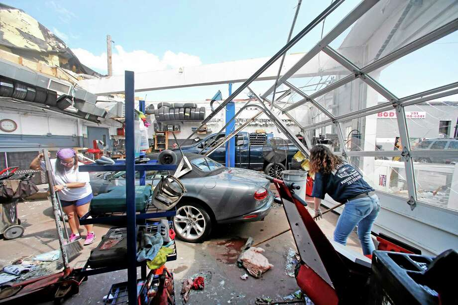 Master Auto manager Marie Annaloro, left, and Victoria Ohlson,right, sweep glass and debris in the service garage where the roof blew off in Revere, Mass. Monday, July 28, 2014, after a tornado touched down. Revere Deputy Fire Chief Mike Viviano says the fire department in that coastal city has received dozens of calls reporting partial building and roof collapses, and downed trees and power lines. Viviano says there are no immediate reports of deaths or serious injuries. (AP Photo/Elise Amendola) Photo: AP / AP