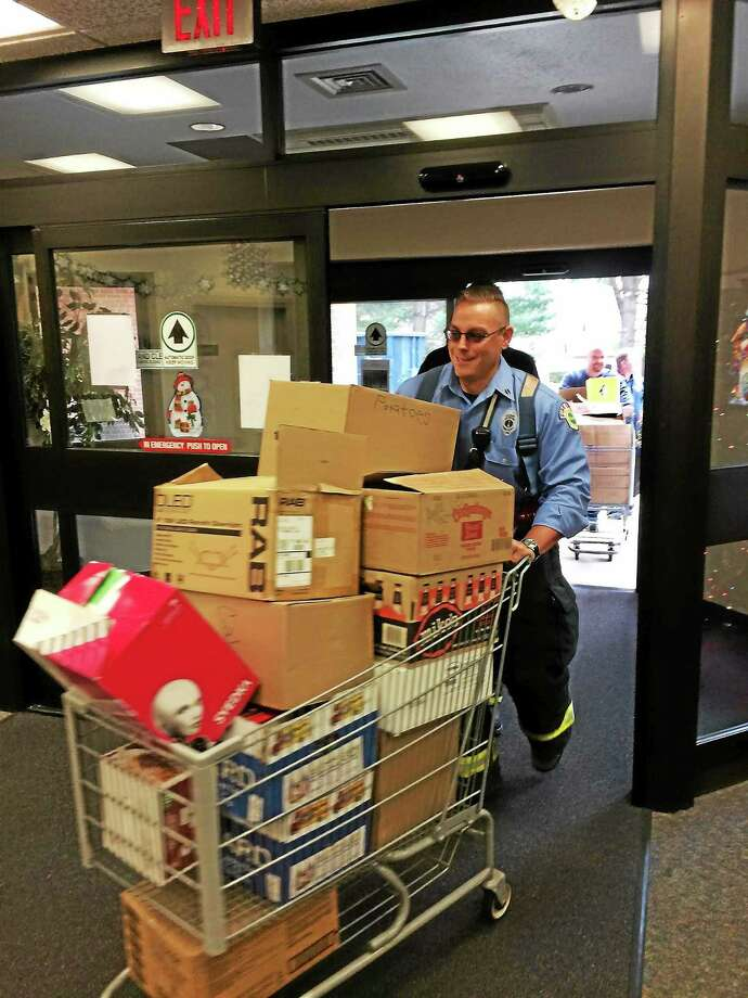 Fire Lt. Matt Sarracco and Assistant Superintendent of Apparatus Jim Lafond, rear, deliver food to Hamden Elderly Services Tuesday morning. Photo: CONTRIBUTED PHOTO — HAMDEN FIRE DEPARTMENT
