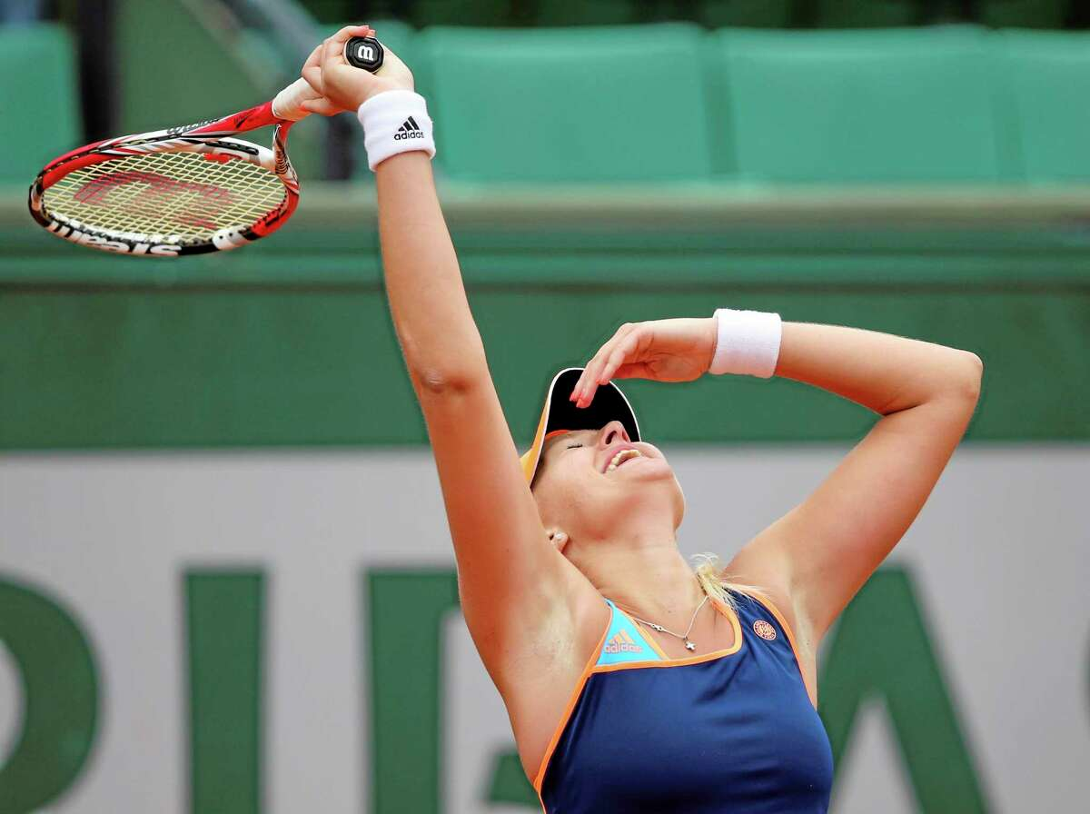 France's Kristina Mladenovic reacts as she defeats China's Li Na during the first round match of the French Open tennis tournament at the Roland Garros stadium, in Paris, France, Tuesday, May 27, 2014. (AP Photo/David Vincent)