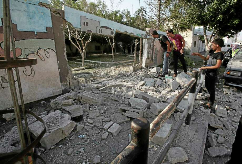 Palestinians inspect the destroyed wall of Shifa hospital after an Israeli air strike, in Gaza, in the northern Gaza Strip, Monday, July 28, 2014.  (AP Photo/Adel Hana) Photo: AP / AP