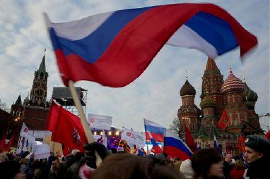 Pro-Putin demonstrators wave Russian national flags as they gather towards to Red Square in Moscow, Russia, Friday, March 7, 2014, with Spassky Tower, left, and St. Basile Cathedral, right, are in the background. Russia rallied support Friday for a Crimean bid to secede from Ukraine, with a leader of Russia?s parliament assuring her Crimean counterpart that the region would be welcomed as ?an absolutely equal subject of the Russian Federation.? Across Red Square, 65,000 people waved Russian flags, chanting ?Crimea is Russia!?(AP Photo/Alexander Zemlianichenko) Photo: AP / AP