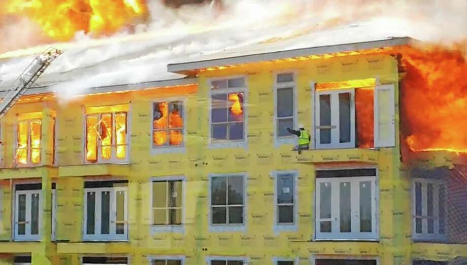 In this image taken from video provided by Karen Jones, a worker waves to rescue workers for help from the fifth floor balcony before swinging down to the one below as firefighters battle a five-alarm fire at a construction site Tuesday, March 25, 2014, in Houston. The cellphone video, shot by Karen Jones from her nearby office, shows the dramatic rescue of the worker from the burning apartment complex that was under construction. (AP Photo/Karen Jones) NO SALES Photo: AP / Karen Jones