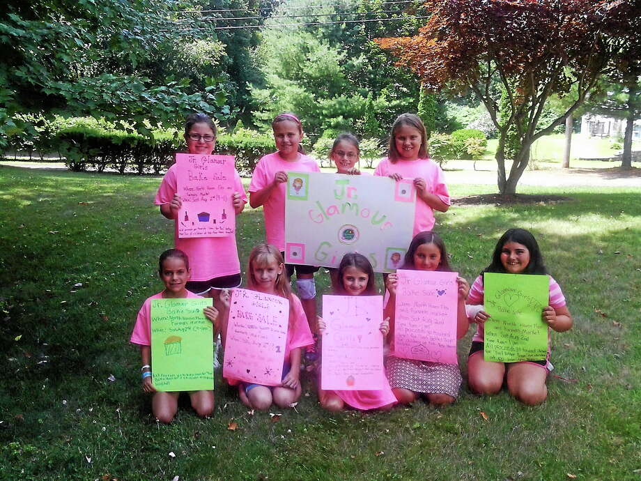 Back row, from left, Jenna Courville, Erin Knapp, Alexis Knapp and Elizabeth Knapp; and, front row, from left, Madison Kararas, Brooke Plummer, Maxine Samperi and Mandy and Meadow Carbone — the Jr. Glamour Girls — hold up signs made for fundraising. Photo: Ebony Walmsley — New Haven Register