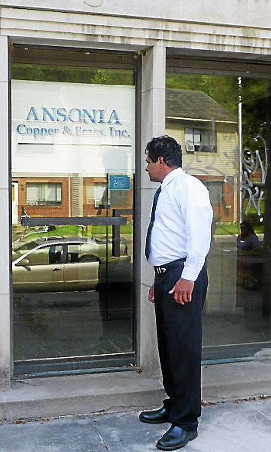 Ansonia Mayor David S. Cassetti peers Monday into the former offices of Ansonia Copper and Brass at 75 Liberty St., one of the sites slated for redevelopment. Photo: Patricia Villers — NEW HAVEN REGISTER