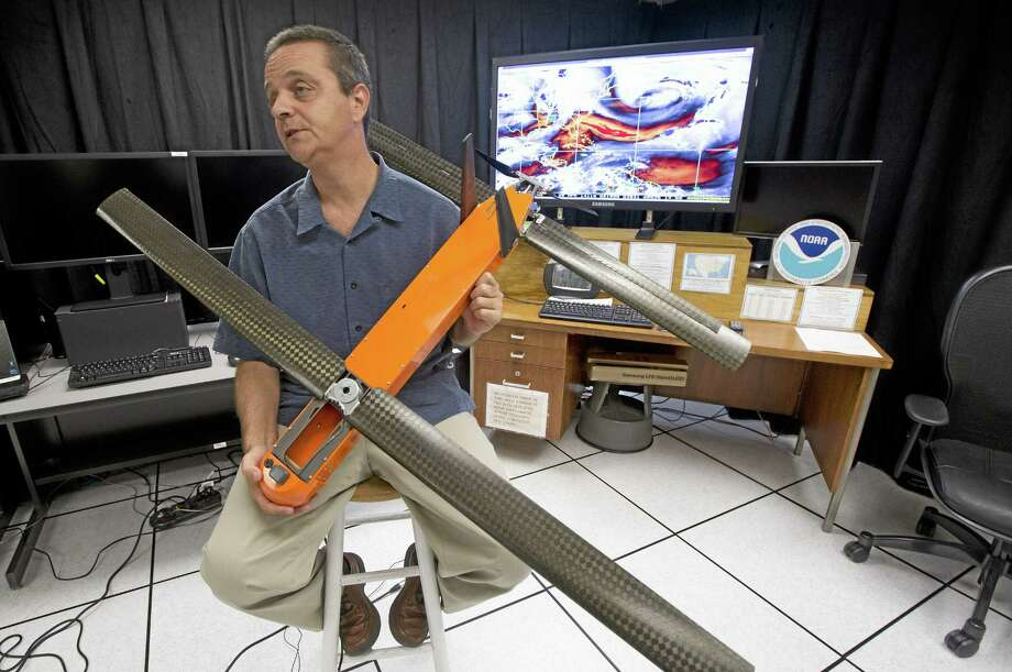 In this April 29, 2014 file photo, Joe Cione, who studies how storms interact with the ocean at the National Oceanic and Atmospheric Administrationís Hurricane Research Division in Miami, displays a drone he hopes to use this hurricane season for research. NOAA researchers plan to test five or six drones in the peak of hurricane season that will be transmitting data that could help forecasters understand what makes some storms fizzle while others strengthen into monsters. Photo: Associated Press   / AP