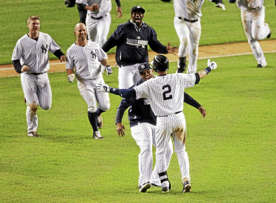 Derek Jeter (2) celebrates with teammates after driving in the winning run against the Orioles Thursday in his final game at Yankee Stadium. Photo: Bill Kostroun — The Associated Press   / AP