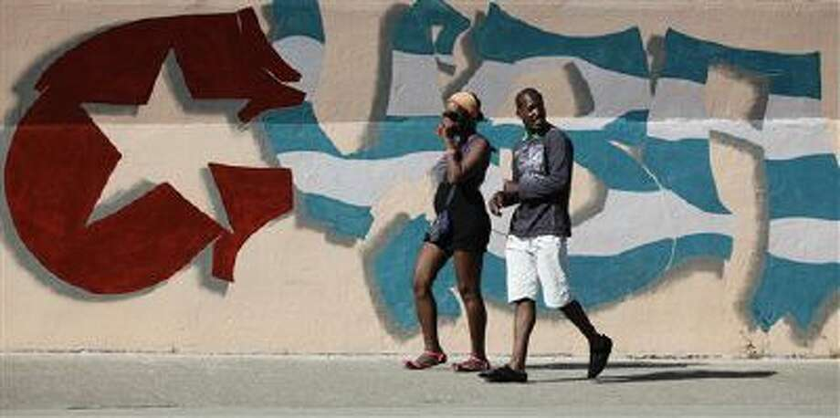Two people walk in front of a national flag mural transformed into the word Cuba, in Havana, Cuba, Sunday. Photo: AP / AP