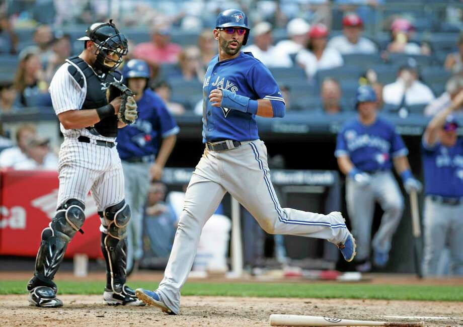 Yankees catcher Francisco Cervelli, left, looks down as Toronto's Jose Bautista scores on Dioner Navarro's  go-ahead, ninth-inning RBI single Sunday. Photo: Kathy Willens — The Associated Press   / AP