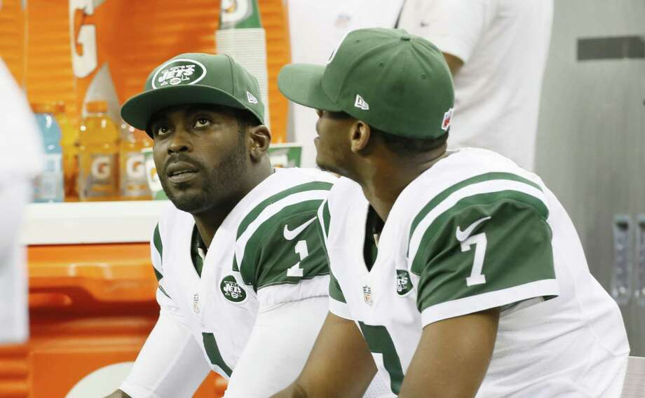 Jets quarterbacks Michael Vick (1) and Geno Smith (7) are seen on the bench during the second half Monday night. Photo: Paul Sancya — The Associated Press   / AP