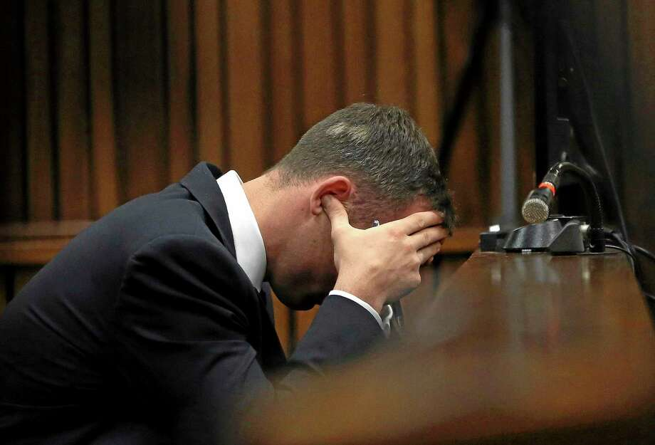 Oscar Pistorius holds his head in his hands during the testimony of a ballistics expert last week. Photo: AP File Photo — Themba Hadebe   / AP POOL