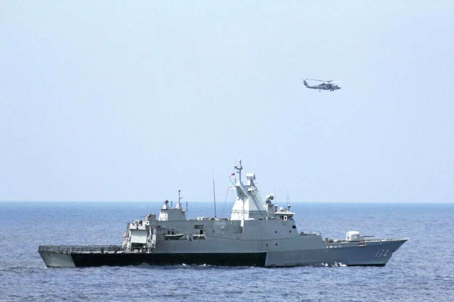 This photo provided by the U.S. Navy shows the Royal Malaysian Navy corvette KD Terengganu and a U.S. Navy MH-60R Sea Hawk helicopter conduct a coordinated air and sea search for a missing Malaysian  Airlines jet in the Gulf of Thailand.  (AP Photo/U.S. Navy, Operations Specialist 1st Class Claudia Franco) Photo: AP / U.S. Navy