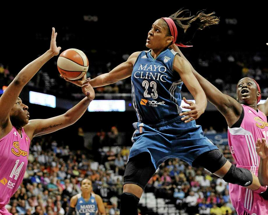 Maya Moore, center, glides to the basket as the Sun's Kelsey Bone, left, and Chiney Ogwumike, right, defend during the second half Sunday in Uncasville. Photo: Jessica Hill — The Associated Press   / FR125654 AP