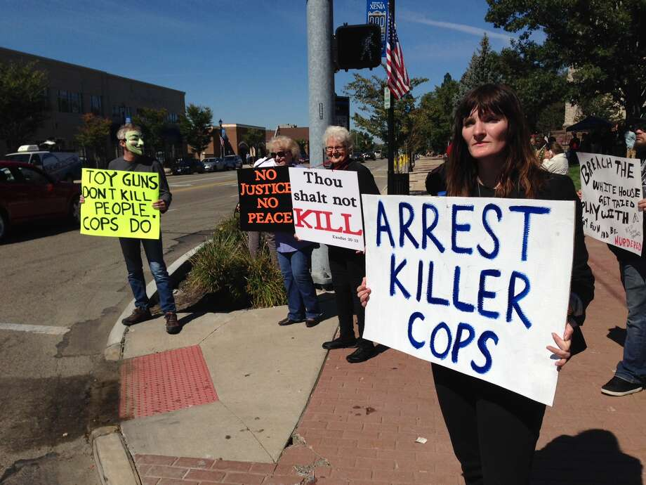 About 100 people rally in support of John Crawford Jr. and his family in their pursuit for answers into the Aug. 5 shooting of John Crawford III, in Beavercreek,, Ohio, Monday, Sept. 22, 2014. The rally coincides with the selection of the special grand jury that will consider evidence and decide whether any criminal charges should be filed in the fatal police officer-involved shooting.  (AP Photo/The Daily News, Ty Greenlees) Photo: AP / The Daily News