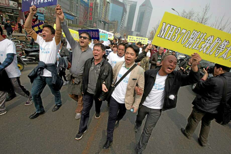 "Relatives of Chinese passengers onboard the Malaysia Airlines plane, MH370 protest with placards one of which reads "" MH370, Don't let us wait too long"" as they march towards the Malaysian embassy in Beijing, China, Tuesday, March 25, 2014.  Furious that Malaysia has declared their loved ones lost in a plane crash without physical evidence, Chinese relatives of the missing marched Tuesday to the Malaysia Embassy, where they threw plastic water bottles, tried to rush the gate and chanted, ""Liars!"" (AP Photo/Ng Han Guan) Photo: AP / AP"