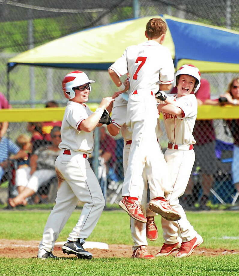 Fairfield American Little League's Jamie Flink, left, Jack Steed ,center, and Brian Kiremidjian, right, celebrate with teammate Brain Howell after beating South Windsor on Sunday. Photo: Mary Albl — Register
