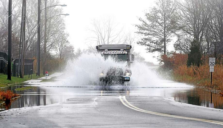 A truck drives through standing water on First Avenue in West Haven Monday. Photo: Arnold Gold — New Haven Register