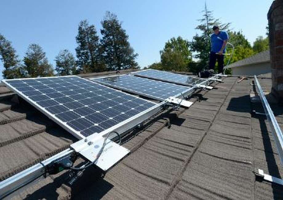 Keith Mitchell, of A-1 Solar Power, does electrical work as and two others install photovoltaic panels on the roof of a home in Concord, Calif. Photo: Bay Area News Group / Bay Area News Group