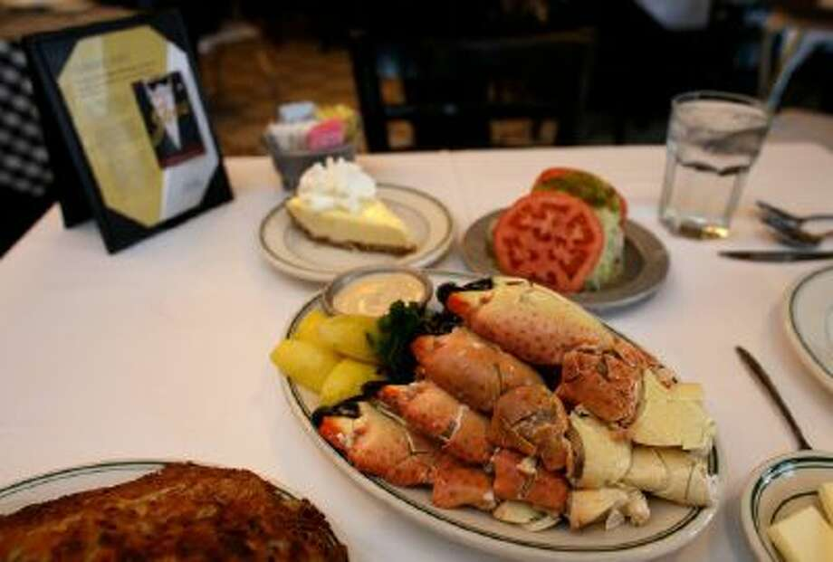 A plate of stone crabs with a serving of hash browns, cole slaw and Key lime pie.