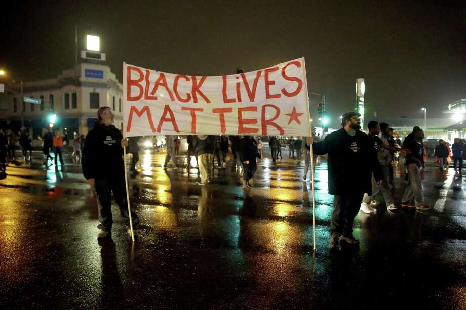 Protesters stand in the middle of a busy intersection blocking traffic Sunday, Nov. 23, 2014, in St. Louis. Ferguson and the St. Louis region are on edge in anticipation of the announcement by a grand jury whether to criminally charge officer Darren Wilson in the killing of 18-year-old Michael Brown. (AP Photo/Jeff Roberson) Photo: AP / AP