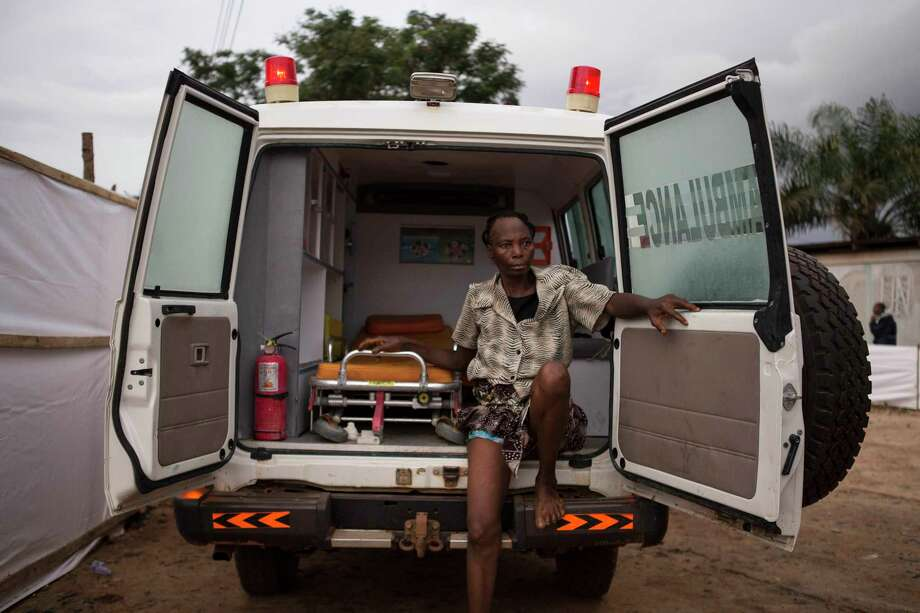 """In this photo taken on Wednesday, Sept. 24, 2014, a woman suspected of suffering from the Ebola virus sits in an ambulance in Kenema, Sierra Leone. Sierra Leone restricted travel Thursday, Sept. 25, 2014 in three more """"hotspots"""" of Ebola where more than 1 million people live, meaning about a third of the country's population is now under quarantine. Sierra Leone is one of the hardest hit countries in the Ebola outbreak sweeping West Africa that is believed to have killed more than 2,900 people, according to World Health Organization tolls published Thursday. (AP Photo/ Tanya Bindra) Photo: AP / AP"""