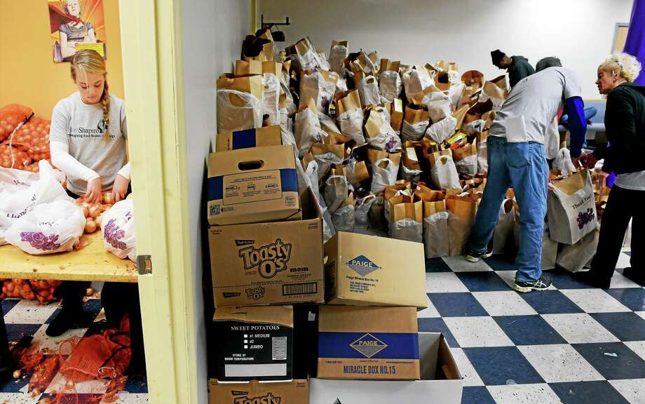 (Photo by Peter Hvizdak - New Haven Register) Jenna Walsh of Orange, 12, the daughter of a BlumShapiro employee,  packages onions  to be put  in over 2,000 bags of donated food Saturday, November 22, 2014 at Casa de Oracion y Adoracion church in New Haven that will be distributed, with turkeys, by Christian Community Action to seniors and families in need in New Haven for Thanksgiving Week.  BlumShapiro and other business and organizations have assisted Christian Community  Action, a faith-based not-for-profit ecumenical social services agency in New Haven.   The food was packaged by volunteers from BlumShapiro during the company's third annual BlumShapiro Thanksgiving food Basket Campaign for Christian Community Action. Photo: Peter Hvizdak — New Haven Register / ©2014 Peter Hvizdak