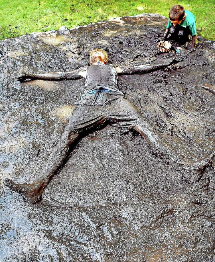 Ranger Mike Karolkowski makes a mud angel in fresh mud during the Mud Madness event at the Ansonia Nature Center Sunday. Photo: Arnold Gold — New Haven Register
