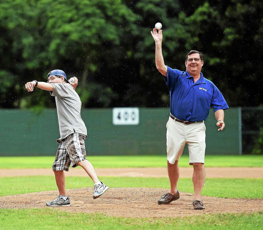 (Peter Casolino-New Haven Register)   West Haven Mayor Edward O'Brien, right, and Special Olympic Athlete, Scott Steffen, deliver the ceremonial first pitch at Quigley Stadium in West Haven. The West Haven Twilight league celebrated the inaugural Mario Peruzzi day before the game between Columbus Auto Body and Flanagan Associates. Mario Peruzzi worked at the stadium for many years and was also a long time coach for Team West Haven, Inc., that sent athletes to the Special Olympics. July 26, 2014. pcasolino@newhavenregister.com Photo: Journal Register Co.