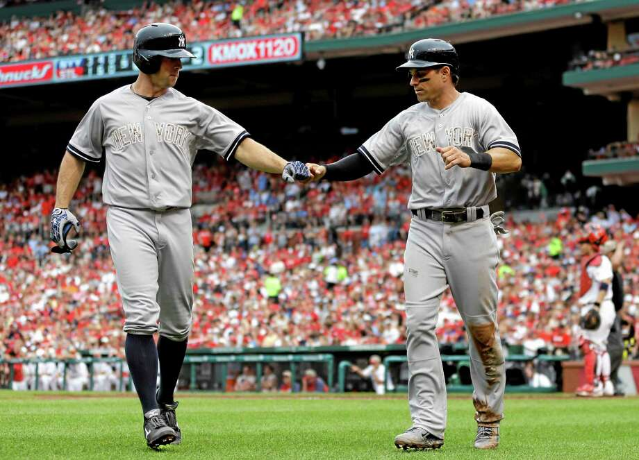 The Yankees' Brett Gardner, left, and Brian Roberts celebrate after Roberts scored on sacrifice fly by Gardner during the fifth inning Sunday. Photo: Jeff Roberson — The Associated Press   / AP