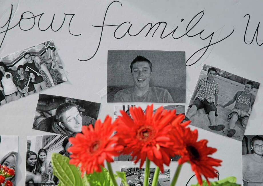 Images of Christopher Martinez are displayed as part of a memorial in front of the IV Deli Mart, where part of Friday night's mass shooting took place, on Sunday, May 25, 2014, in the Isla Vista beach community of Santa Barbara, Calif. Sheriff's officials said Elliot Rodger, 22, went on a rampage near the University of California, Santa Barbara, stabbing three people to death at his apartment before shooting and killing three more in a crime spree through a nearby neighborhood. (AP Photo/Chris Carlson) Photo: AP / AP