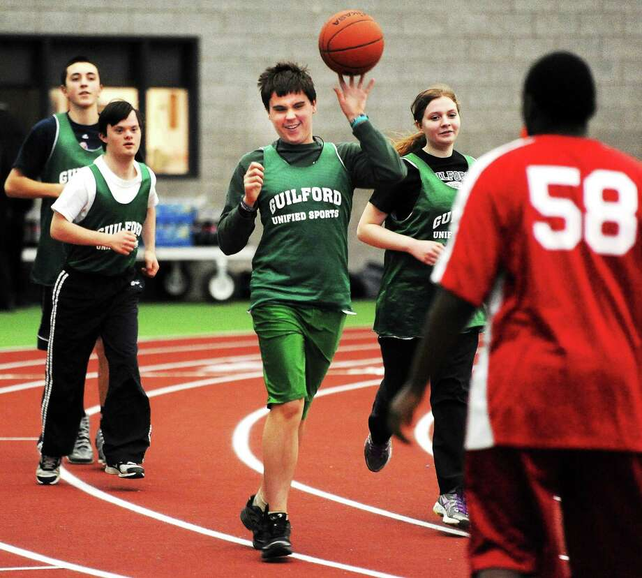 The SCC held its Unified basketball tournament at the Floyd Little Athletic Center in New Haven on Monday. Pictured, from left, are John Suchy, Lee Owens, Nick Smith-Romanski and Audrey Balaska of Guilford and Cheshire's Keymothie Hough. Photo: Mara Lavitt — Register   / Mara Lavitt
