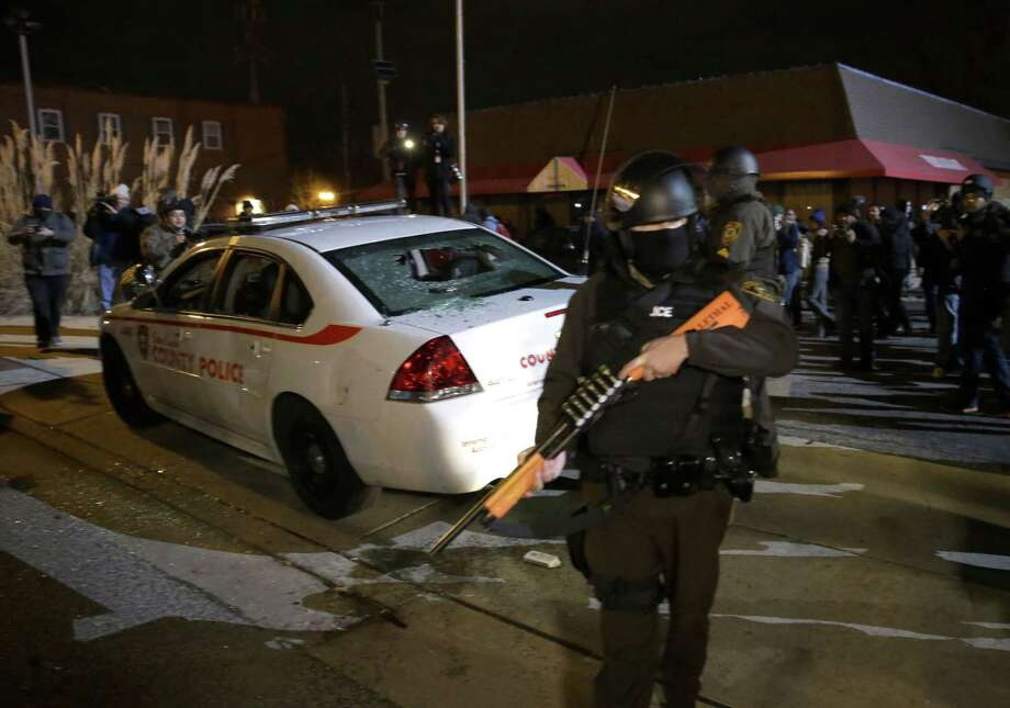 An armed police officer guards the area after a group of protesters vandalize a police cruiser after the announcement of the grand jury decision not to indict police officer Darren Wilson in the fatal shooting of Michael Brown, an unarmed black 18-year-old, Monday, Nov. 24, 2014, in Ferguson, Mo. Photo: (AP Photo/David Goldman) / AP