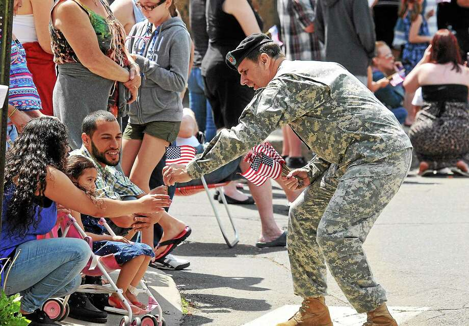 Rob Salisbury, a retired Army MP sergeant, hands out candy during the annual West Haven Memorial Day Parade Monday. Photo: Peter Casolino — New Haven Register