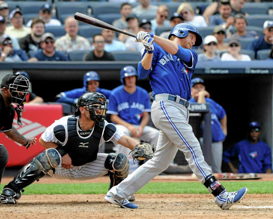 The Toronto Blue Jays' Dan Johnson hits a three-run home run as Yankees catcher Francisco Cervelli looks on during the ninth inning of Saturday's game at Yankee Stadium in New York. Photo: Bill Kostroun — The Associated Press   / FR51951 AP