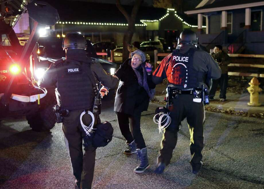 Police officers grab a protester after the announcement of the grand jury decision Monday, Nov. 24, 2014, in Ferguson, Mo. A grand jury has decided not to indict Ferguson police officer Darren Wilson in the death of Michael Brown, the unarmed, black 18-year-old whose fatal shooting sparked sometimes violent protests. Photo: (AP Photo/David Goldman) / AP