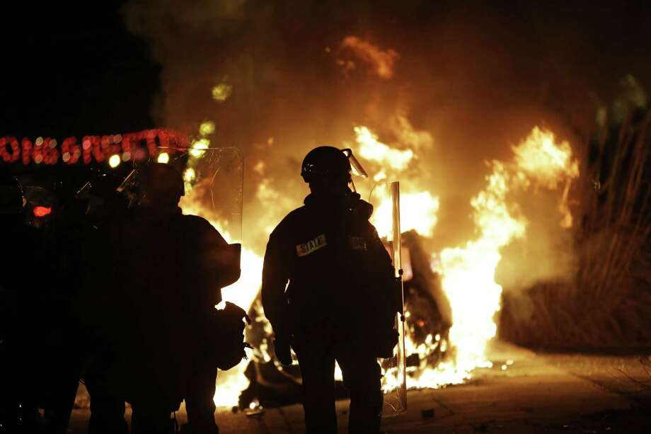 Police in riot gear move down the street past a burning police car, Monday, Nov. 24, 2014, in Ferguson, Mo. A grand jury has decided not to indict Ferguson police officer Darren Wilson in the shooting death of 18-year-old Michael Brown. Photo: (AP Photo/David Goldman) / AP