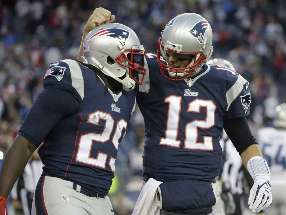 Patriots quarterback Tom Brady, right, congratulates running back LeGarrette Blount on his touchdown in the fourth quarter Sunday. Photo: Steve Senne — The Associated Press    / AP