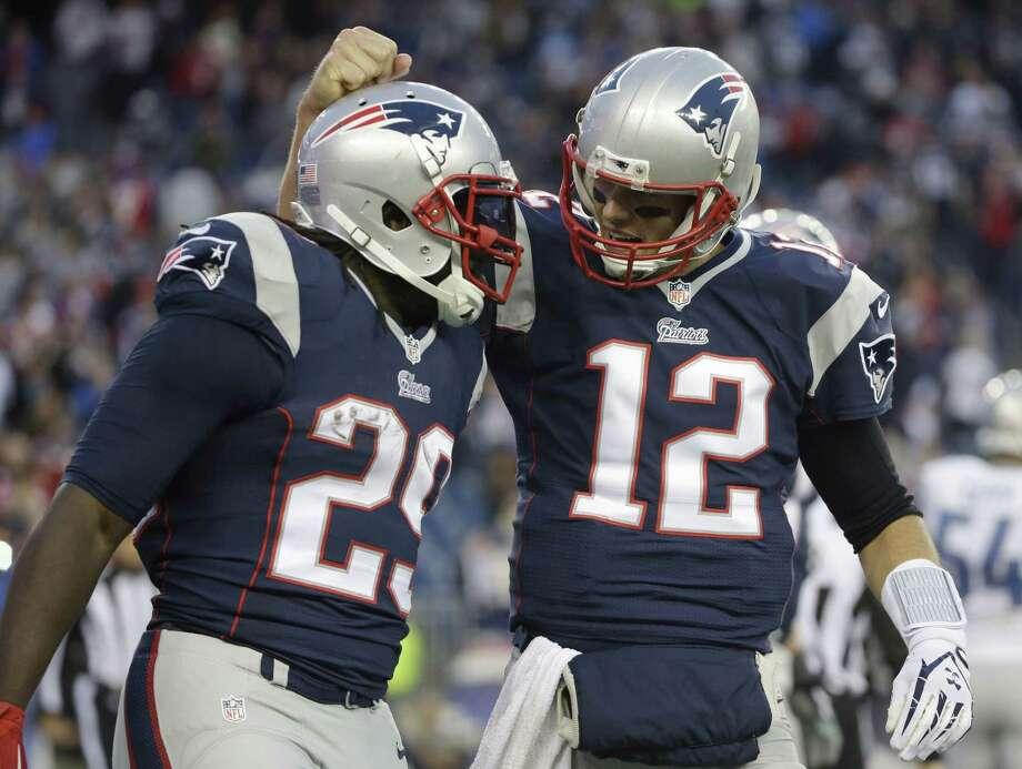 Patriots quarterback Tom Brady, right, congratulates running back LeGarrette Blount on his touchdown in the fourth quarter Sunday. Photo: Steve Senne — The Associated Press    / AP