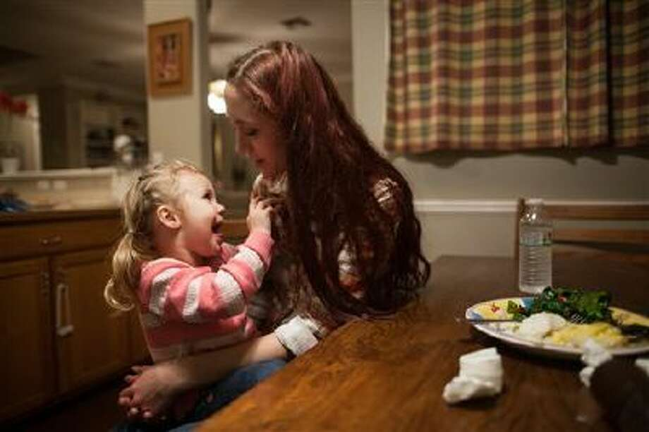 Maggie Barcellano sits down for dinner with her daughter, Zoe, 3, in Austin, Texas. Barcellano, who lives with her father, enrolled in the food stamps program to help save up for paramedic training while she works as a home health aide and raises her daughter. Working-age people now make up the majority in U.S. households that rely on food stamps, a switch from a few years ago when children and the elderly were the main recipients. Photo: AP / FR170773 AP