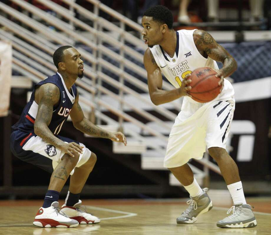 UConn guard Ryan Boatright, left, pressures West Virginia guard Terrence Phillip during Sunday's game. Photo: Ricardo Arduengo — The Associated Press   / AP