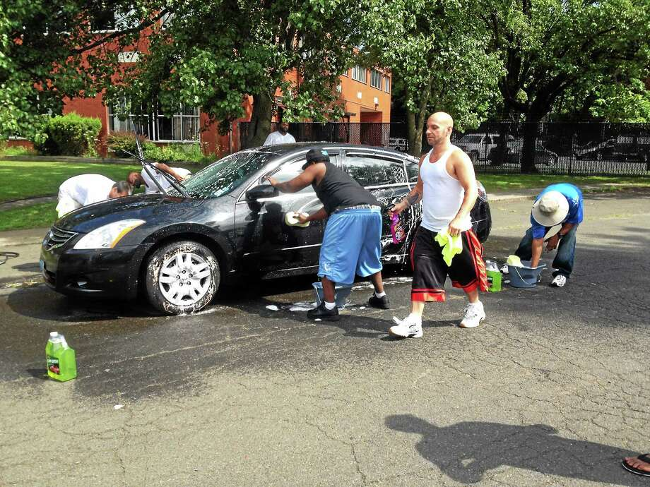 Former prisoners from the Men Empowering Men support group wash cars for free at the Dixwell Fire Station Saturday. They took donations for the state Office of Victim Services. Photo: Kristin Stoller - New Haven Register