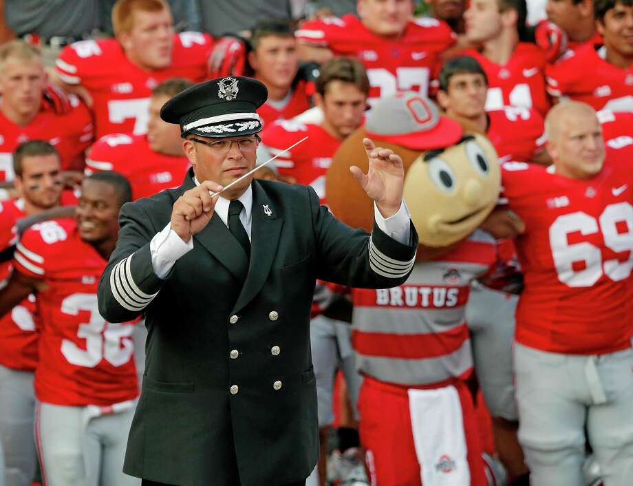 "In this Sept. 7, 2013 photo, Ohio State University marching band director Jon Waters leads the band in ""Carmen Ohio"" following a NCAA football game against San Diego State at Ohio Stadium in Columbus, Ohio. OSU on Thursday, July 24, 2014 fired Waters amid allegations he knew about and ignored ""serious cultural issues"" including sexual harassment. (AP Photo/The Columbus Dispatch, Adam Cairns) Photo: AP / The Columbus Dispatch"