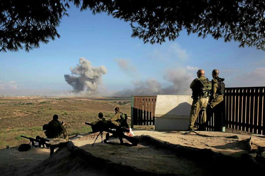 """Israeli soldiers observe bombings of Gaza before a 12-hour cease-fire, seen from the border of Israel and the Gaza Strip, Saturday, July 26, 2014. Gaza residents used a 12-hour humanitarian cease-fire on Saturday to stock up on supplies and survey the devastation from nearly three weeks of fighting, as they braced for a resumption of Israel's war on Hamas amid stalled efforts to secure a longer truce. The Israeli military said its troops """"shall respond if terrorists choose to exploit"""" the lull to attack Israeli soldiers or civilians. Photo: (Tsafrir Abayov — The Associated Press) / AP"""