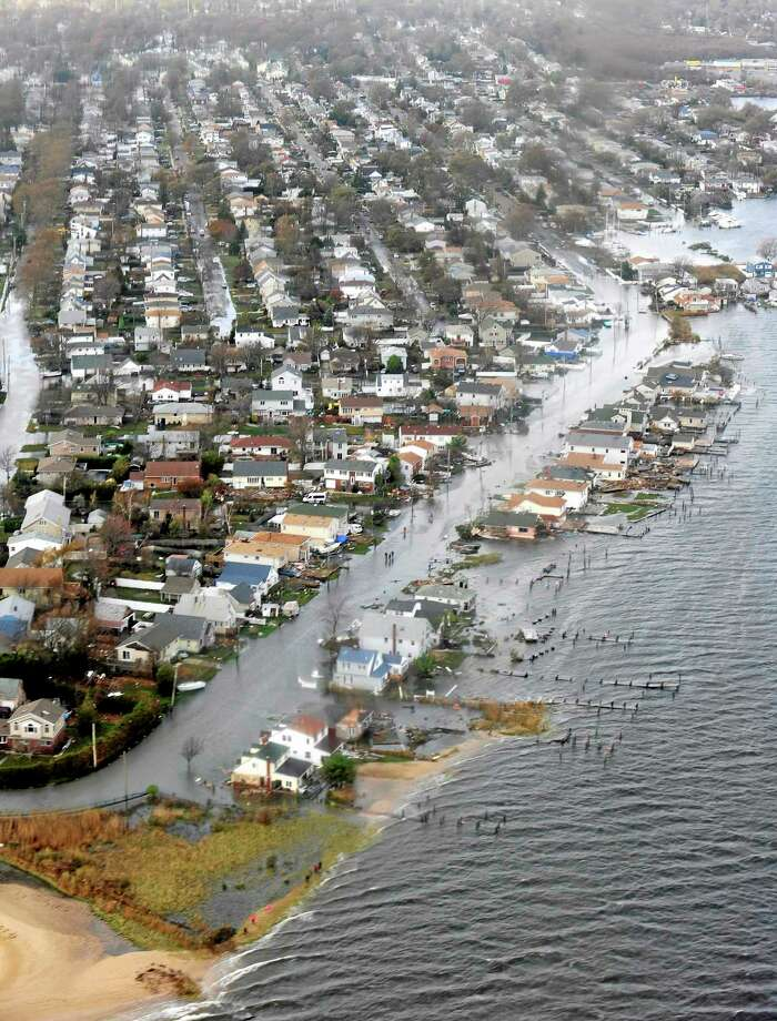 This Oct. 30, 2012 aerial photo provided by the U.S. Coast Guard shows storm damage from Superstorm Sandy in a portion of New Haven, Conn. In 2012, Congress passed a law requiring approximately 1.1 million policyholders nationwide to start paying rates based on the true risk of flooding. Nearly 4,200 policyholders in Connecticut face increases of up to 25 percent each year. More than 14,000 property owners in the state will be hit with annual premium increases as high as 18 percent annually, until the policyholder switches to a risk-based rate. (AP Photo/U.S. Coast Guard, Petty Officer 2nd Class Rob Simpson, File) Photo: AP / U.S. Coast Guard
