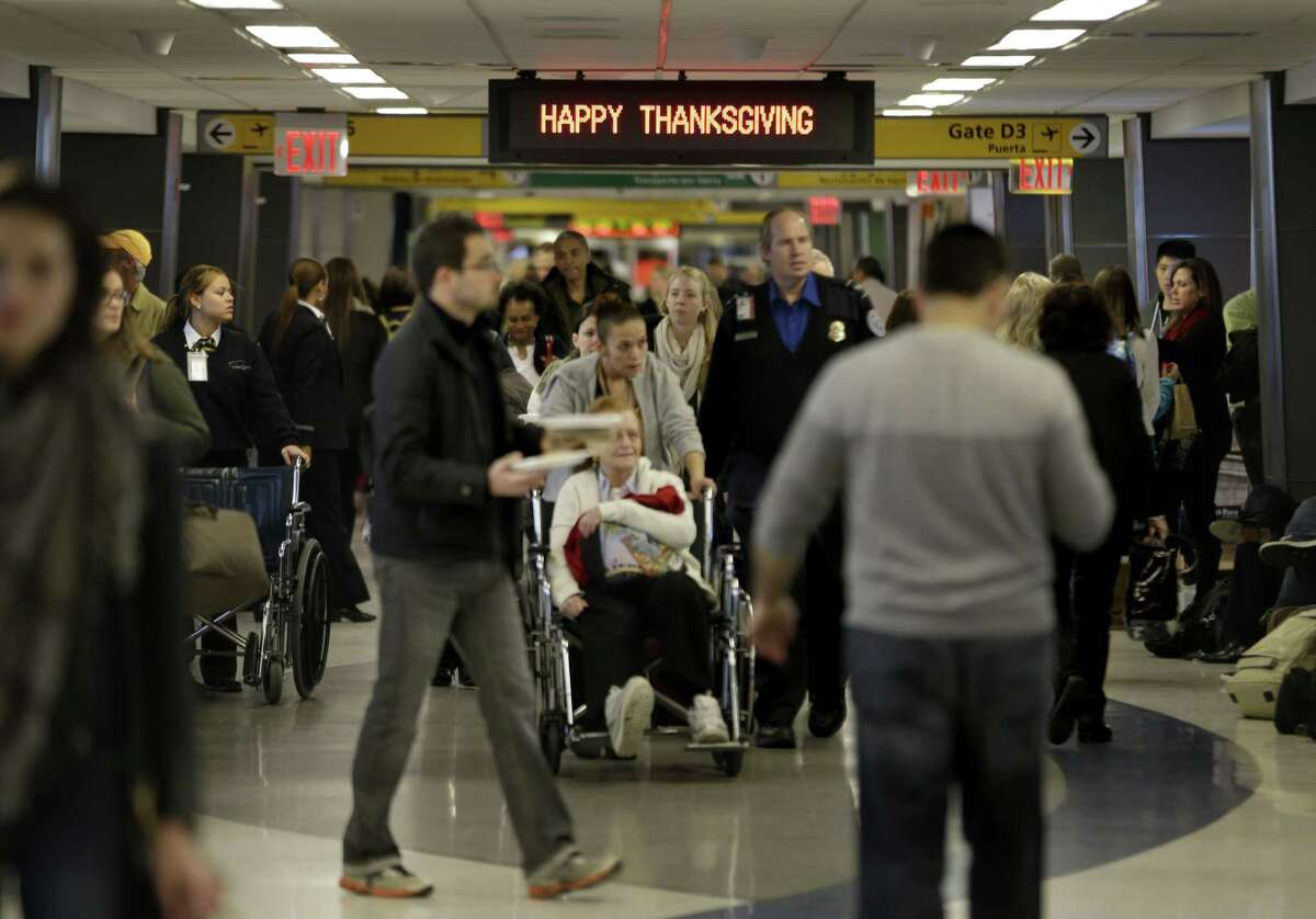 "FILE - In this Nov. 26, 2013, file photo, travelers walk under a sign reading ""Happy Thanksgiving"" at LaGuardia Airport in New York. There will be 12.3 million roundtrip passengers, globally, on U.S. airlines during the 2014 holiday travel period, up 1.5 percent from 2013, according to the industryís lobbying group, Airlines for America."