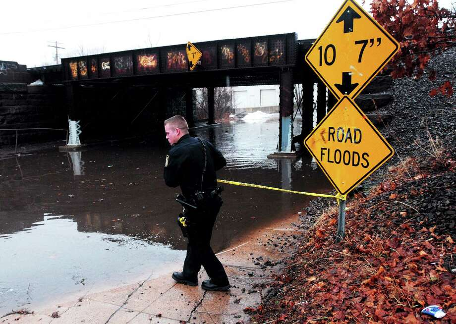 (Arnold Gold ó New Haven Register)  West Haven Police Officer Justin Standish puts police tape across a flooded portion of Washington Ave. in West Haven after a downpour on 1/11/2014. Photo: Journal Register Co.