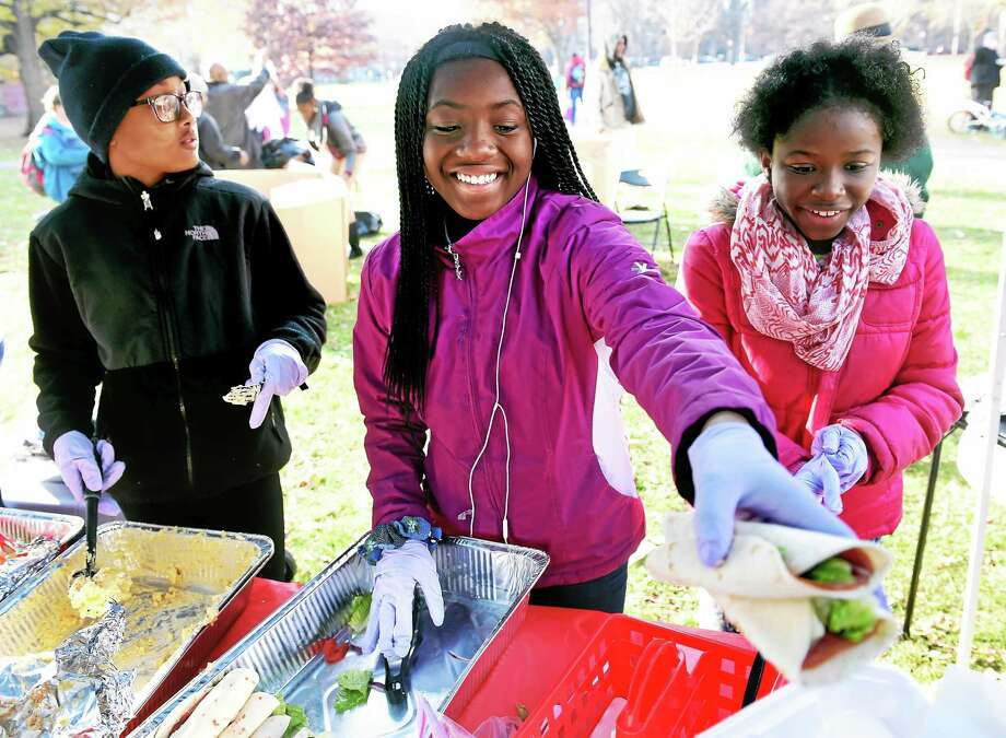 (Arnold Gold-New Haven Register)   Left to right, Chyna Watts, 11, Zyiara Bradley, 12, and Mahogany Hutchinson of Kidz Kook Association serve lunch to the homeless on the New Haven Green on 11/23/2014. Photo: Journal Register Co.