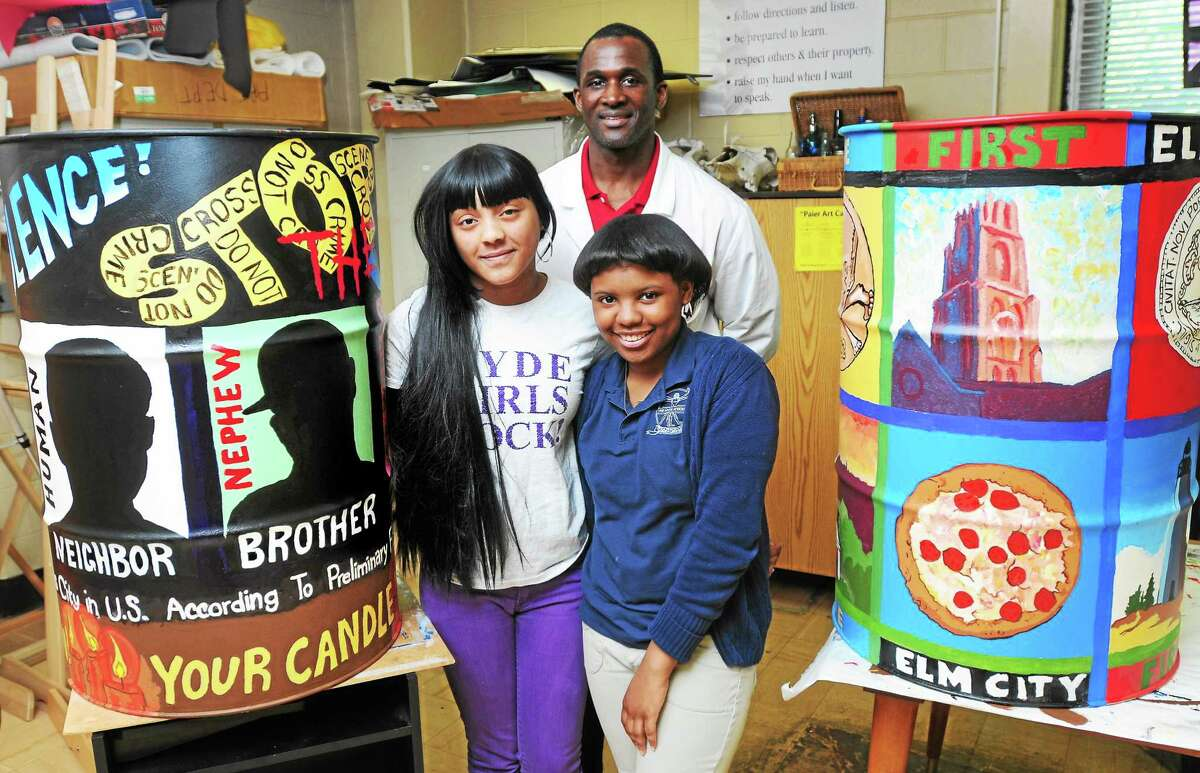 Charlene Tobias, left, 18, and Tyana Lesane, right, 17, with their art teacher Patrick Lawrence and the oil drums they helped paint for the Oil Drum Art project at Hyde School of Health and Sports Medicine in North Haven.