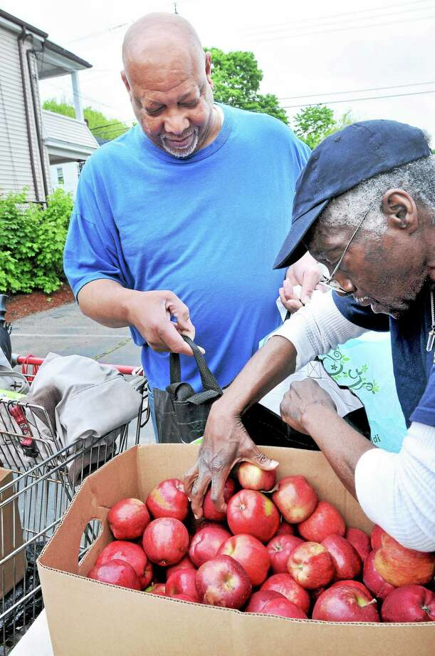 Johnny Ormond (left) of West Haven receives apples from William Moore (right) of Hamden during a monthly Connecticut Food Bank distribution in Hamden last week. Photo: (Arnold Gold-New Haven Register)
