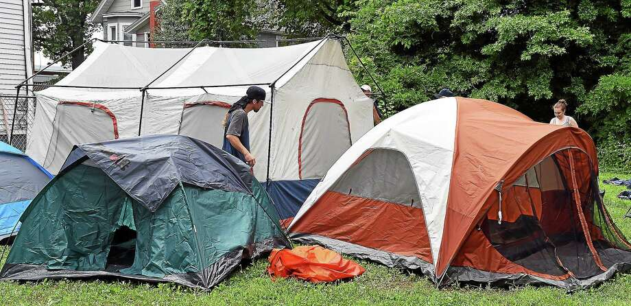 (Peter Casolino-New Haven Register)   New Haven homeless and their advocates from the Catholic Amistad Worker House clean and erect tents at 634 Howard Avenue, a city owned property.  July 24, 2014. pcasolino@newhavenregister.com Photo: Journal Register Co.