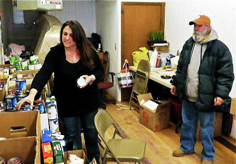 Stratford resident Missy Samaha, a volunteer, checks expiration dates on food donations. With her is Shelton resident Steve Serrato, one of 29 people who lost their belongings in the Jan. 6 fire that destroyed a block on Howe Avenue in Shelton. Patricia Villers/Register Photo: Journal Register Co.